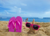 Girl's Flip flops and starfish with sunglasses on sandy beach. With playing girl by the ocean on the background in Hawaii Royalty Free Stock Photos