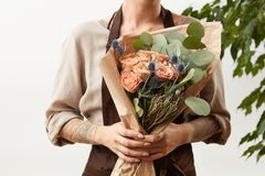 Woman`s hands with tattoo hold flower roses bouquet for congratulation on a light background, place for text. Greeting. Girl`s florist hands hold fresh natural stock photography