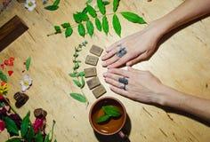 Girl& x27; s-Hände, Runen und heißer tadelloser Tee stockfotos