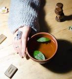 Girl& x27; s-Hände, Runen und heißer tadelloser Tee lizenzfreie stockfotos