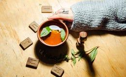 Girl& x27; s-Hände, Runen und heißer tadelloser Tee stockfotografie