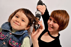 Girl's hair. The woman dries girl's hair. The child smiles with pleasure Stock Image