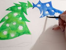 The girl`s hand draws a blue and green fir-tree with a watercolor paint royalty free stock photography