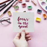 Girl`s hand holding card with inspirational quote. Focus on the good written in calligraphy style. Artist workspace on a pink background. Flat lay Royalty Free Stock Image