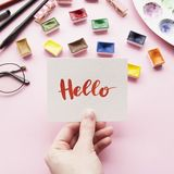 Girl`s hand holding card with word. Hello written in calligraphy style. Artist workspace on a pink background. Flat lay Stock Photography