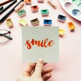 Girl`s hand holding card with word. Smile written in calligraphy style. Artist workspace on a pale pink pastel background Royalty Free Stock Image
