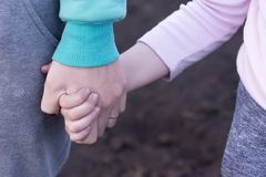Girl`s hand holds baby`s hand. Mother holding her daughter`s hand Royalty Free Stock Image