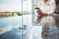 Girl`s hand holds a cup of coffee. the girl is sitting in a cafe royalty free stock photos