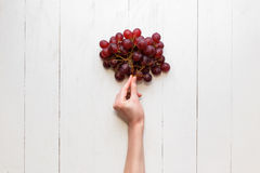 The girl`s hand holds on to a bunch of red grapes on a wooden background. View from above. Grapes are like balloons. Stock Photography