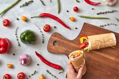 A girl`s hand holds a vegetable burrito Royalty Free Stock Photography