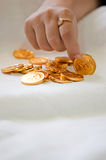 A girl's hand picking up a gold coin from a pile Stock Photo
