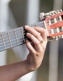 Girl`s hand playing guitar Stock Photos
