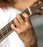 Girl`s hand playing guitar Stock Images