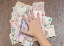 A girl`s hand pressing a bundle of different Asian money to the wooden table. Asian travel concept. Exchange concept. Business concept. Corruption concept Stock Image
