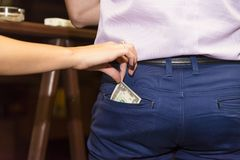 The girl`s hand pulls money. Out of the man`s pocket Royalty Free Stock Image
