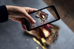 Girl`s hand shoots food dessert on the phone. chocolate pudding cake filled with fresh berries on the Golden tray with folk and royalty free stock photo
