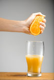 Girl S Hand Squeezing Out Juice From Orange Into Glass. Royalty Free Stock Image