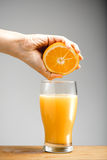 Girl s hand squeezing out juice from orange into glass. Royalty Free Stock Photography