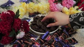 The girl`s hand takes a piece of candy or chocolate from the white plate. Woman`s hands taking the sweet chocolate stock footage