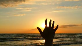 Girl`s hand, touching the sunlight, against the background of the sea sunset. Happy girl looking at the shining sun of. The sunset through his fingers. Slow stock video footage