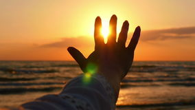Girl`s hand, touching the sunlight, against the background of the sea sunset.