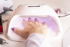 The hands of the girl in the UV lamp for nails on the manicure table stock photo