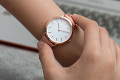 Girl`s hand with wrist watch in front of desk with laptop comput Stock Photography