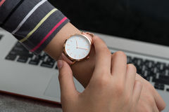 Girl`s hand with wrist watch in front of desk with laptop comput Royalty Free Stock Image
