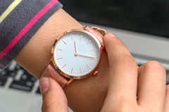 Girl`s hand with wrist watch in front of a laptop computer Stock Photos