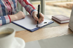 The girl`s hand writes in black pen on a white sheet of paper Royalty Free Stock Photos