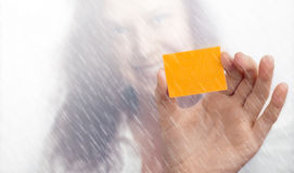 Girl's hand with a yellow slip of paper in the rain Stock Photo