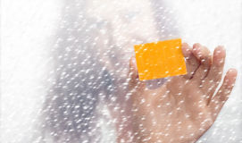 Girl's hand with a yellow slip of paper in the snowfall Royalty Free Stock Photos