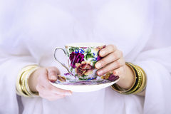 Girl's hands with bracelets  holding a colorful cup Royalty Free Stock Images