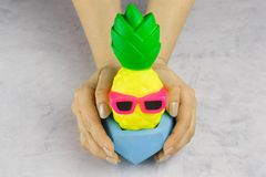 Girl`s hands with bright pineapple with sunglasses. In concrete pot on white background royalty free stock image