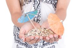 Girl's hands carrying sand with two mini umrellas Royalty Free Stock Photos