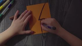 Girl`s hands drawing spider web on a card. Preparing for the celebration of Halloween stock video