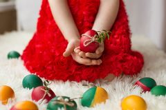 The girl`s hands hold decorated Easter eggs. Hands of a young girl in a red dress holding decorated Easter eggs Stock Image