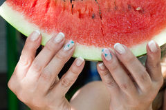 The girl`s hands holding a piece ripe watermelon Stock Photos