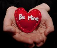 Cupped hands holding a single red heart. A girl`s hands holding a red heart with `Be Mine` written on it the hands are  on a black background Royalty Free Stock Photography