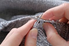 In the girl`s hands incomplete project of knitting and metallic knitting needles close-up. Woman knits a grey woolen sweater. The stock photography