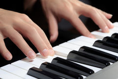 Girl's hands on the keyboard of the piano Stock Photography