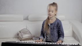 Girl`s hands on the keyboard of the piano. The girl plays piano,close up piano. Hands on the white keys of the Piano. Playing a Melody. Women`s Hands on the stock video