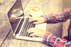 Girl's hands with laptop and coffee mug on a wooden table Royalty Free Stock Image