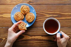 In the girl`s hands and a mug of black tea bitten biscuit. Next to the homemade cinnamon rolls on a blue plate on a wooden table. royalty free stock photos