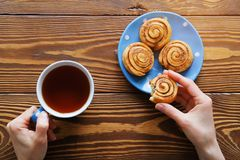 In the girl`s hands and a mug of black tea bitten biscuit. Next to the homemade cinnamon rolls on a blue plate on a wooden table. stock photo