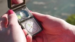 Girl's hands opening multifunctional compass device. Extreme close-up with river stream at background.  stock video