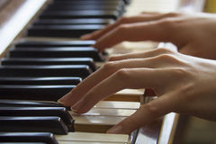 Girl's hands on piano Stock Photography