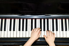Girl's hands and piano keyboard close-up view Stock Photos