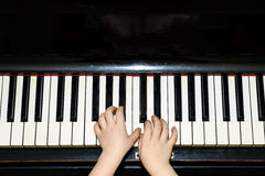 Girl's hands and piano keyboard close-up view Royalty Free Stock Photography