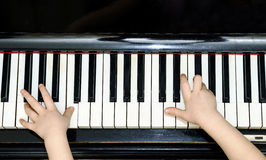 Girl's hands and piano keyboard close-up view Stock Image